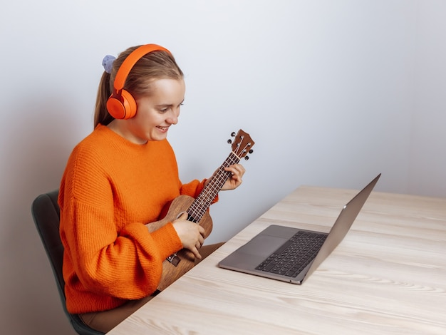 女の子がウクレレをオンラインで演奏するレッスンを受ける