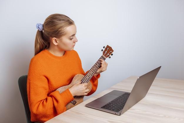 女の子がウクレレをリモートで演奏するレッスンを受けます
