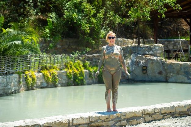 トルコのリゾートで女の子が泥風呂に入る。治療用泥の健康改善。