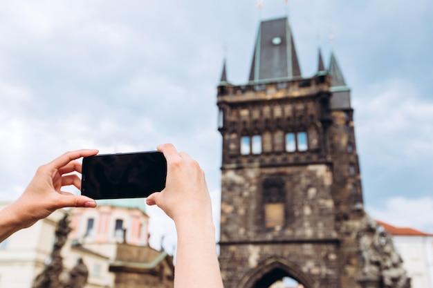 プラハのカレル橋の電話で女の子が写真を撮る
