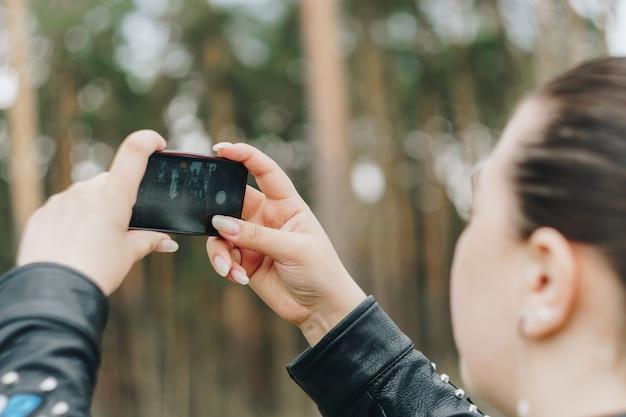 女の子が携帯電話で森の写真を撮る