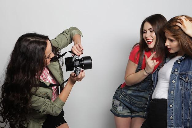 Девушка фотографирует своих друзей. концепция дружбы и веселья. лучшие друзья наслаждаются моментом с современной камерой.