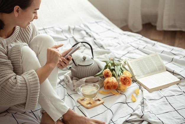 Девушка фотографирует на телефон весеннюю композицию с чаем и тюльпанами в постели. концепция содержания социальных сетей.