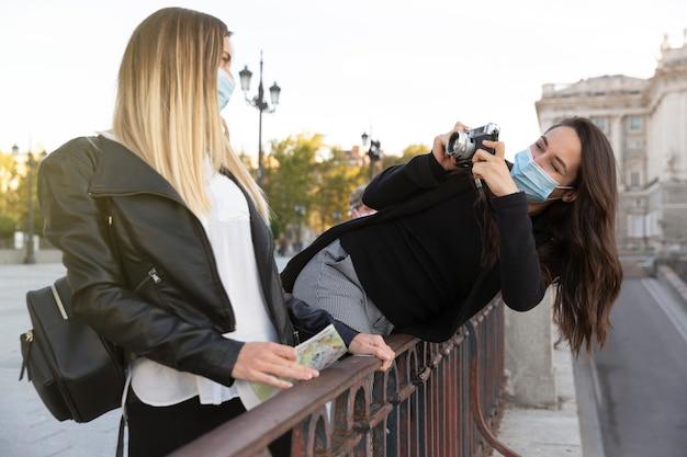 아날로그 카메라로 친구의 사진을 찍는 소녀. 둘 다 안면 마스크를 쓰고 있습니다. 새로운 노멀의 개념.