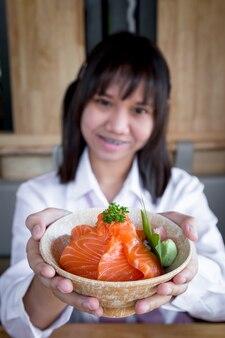 10代の少女のアジア人女性は、サーモンドンが生のサーモンであり、正面にご飯があり、カメラを見て日本食レストランで笑っていることを示しています。セレクティブフォーカス。