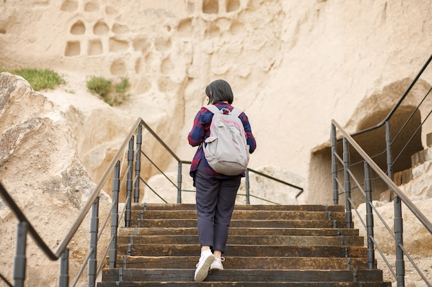 バックパックを背負った少女旅行者が山の丘を登る、歴史的価値