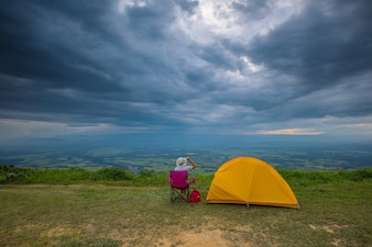 A girl traveler with her tent on the cliff in the evening.