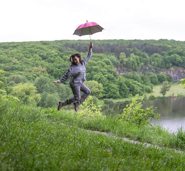 雨天の山岳地帯の湖の近くでジャンプする傘の下の女の子