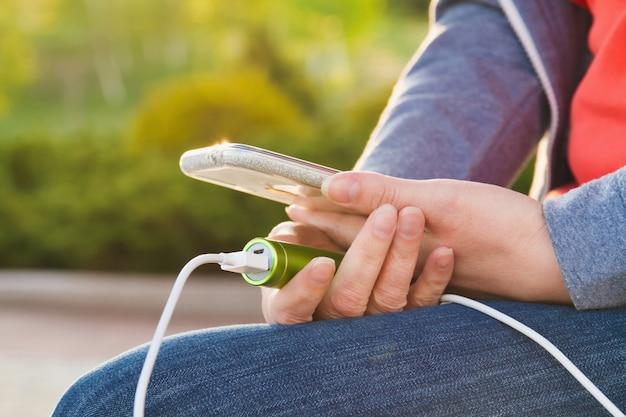 外部のパワーバンクから充電しながら、女の子が屋外でスマートフォンを使用しています