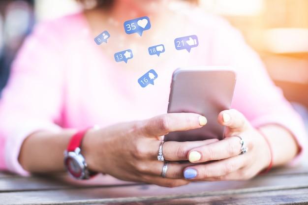 女の子はソーシャルネットワークで時間を過ごし、いいねやチャンネル登録者を獲得しながらスマートフォンを使用します。 Premium写真