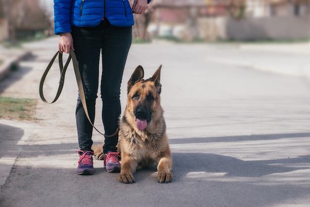Девочка гуляет с собакой на улице. отдых с домашним животным во время карантина. прогулка с немецкой овчаркой по городу на свежем воздухе. копировать пространство