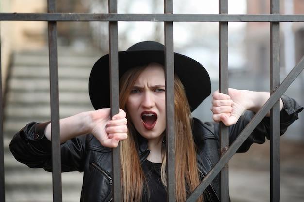Девушка идет по улице города в кожаном жилете с телефоном. молодая красивая девушка в шляпе и с темным макияжем снаружи. девушка в готическом стиле на улице.