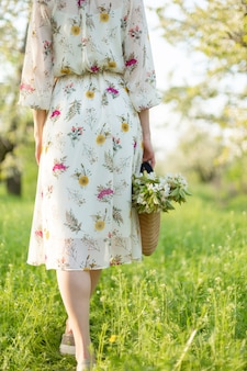 咲く自然を楽しんでいる春の緑豊かな公園を歩く少女