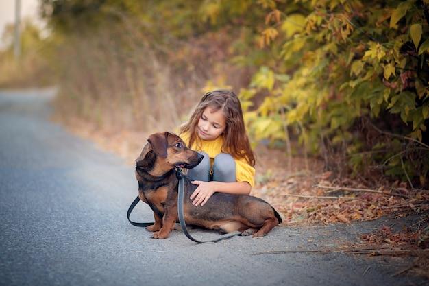 소녀는 닥스 훈트 강아지와 함께 채찍질 가을을 안내합니다.