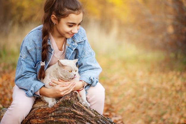 Девушка гуляет по осеннему парку с кошкой на руках