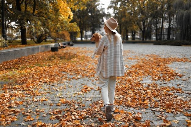 Осенняя листва идет девушка с собакой на руках.