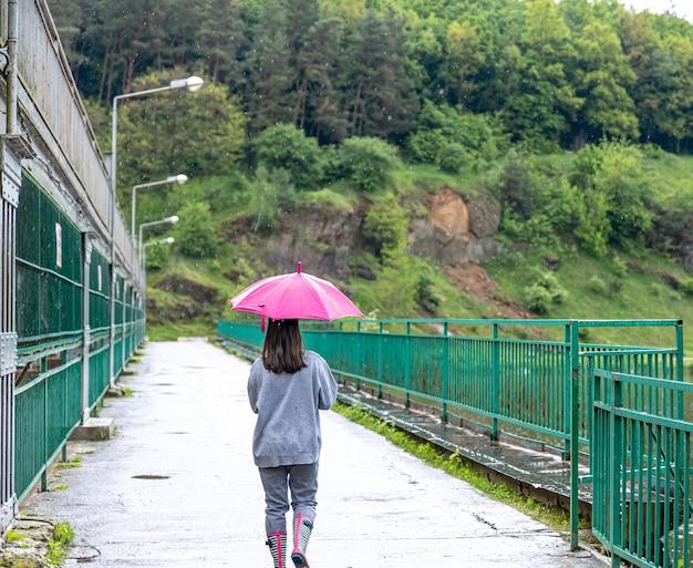 Девушка гуляет под зонтиком в дождливую погоду по мосту в лесу