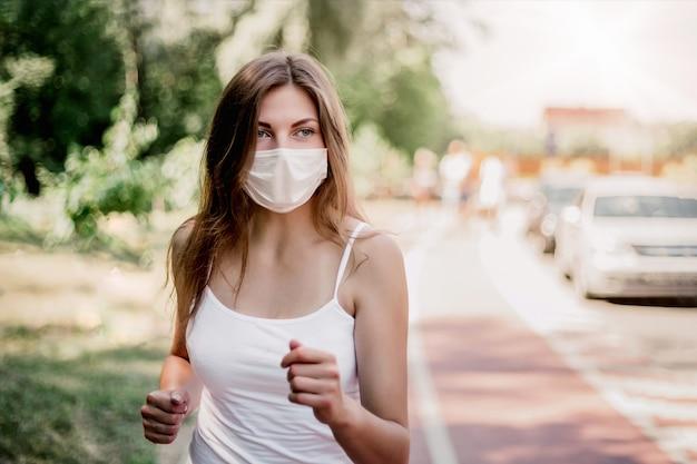 보호 마스크를 착용 한 소녀가 푸른 나무 사이의 아침 공원을 뛰어 다니며 복사 공간, 검역, covid-19를 봅니다.