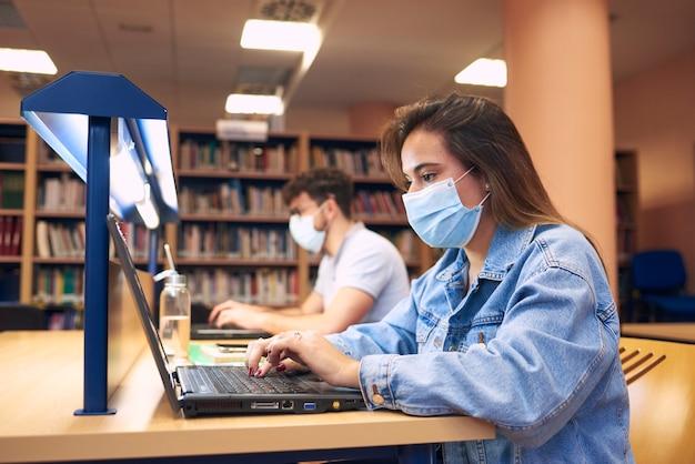 Девушка в масках учится с ноутбуками в библиотеке