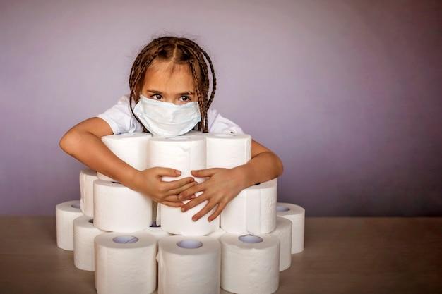 화장지 더미 근처에 앉아있는 인공 호흡기 마스크를 착용하는 소녀는 자기 격리를 준비합니다.