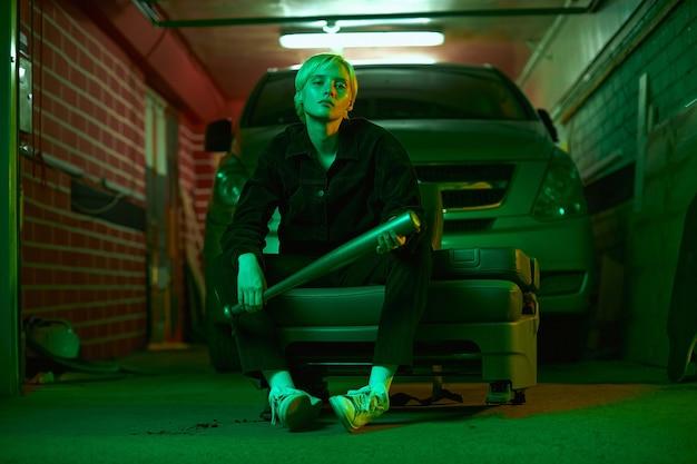 男のように見える女の子が、ネオンで撮影しているガレージで彼女の車の近くに彼女の手でバットを持って座っています...