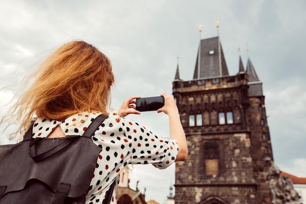 バックパックを持った女の子がプラハのカレル橋の電話で写真を撮っています。観光客の女の子はプラハ城の写真を撮ります。女性はスマートフォンを手に持っています。