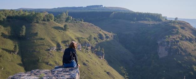 バックパックを背負った少女が崖の端に立っています。山を旅する