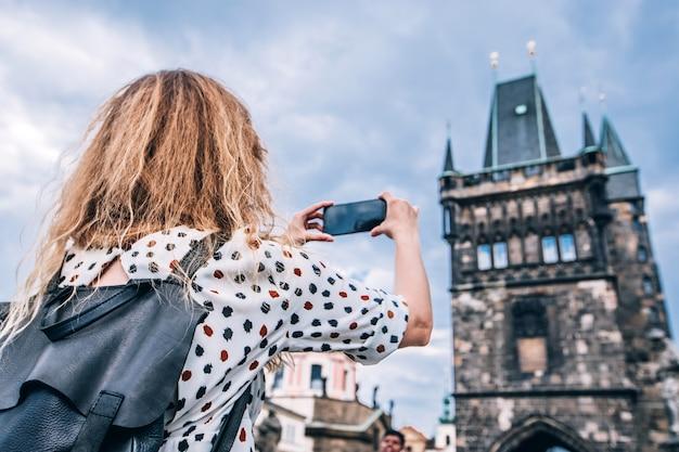 プラハのカレル橋の電話でバックパックを持つ少女が写真を撮る
