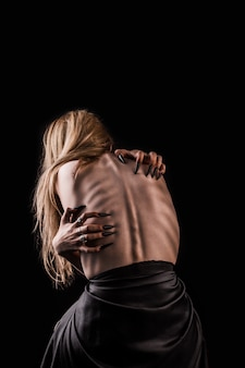 맨 뒤로, 심한 가늘고 튀어 나온 갈비뼈가있는 소녀
