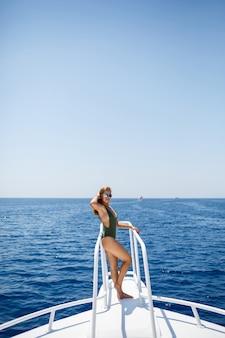 緑の水着姿の美しい姿の女の子。彼女は紅海の白いヨットに乗っています