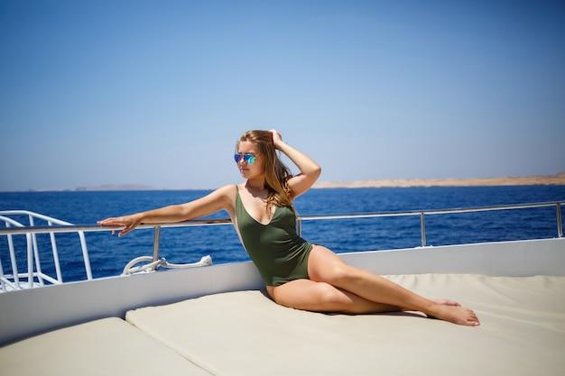 Девушка с красивой фигурой в зеленых купальниках. она на белой яхте в красном море