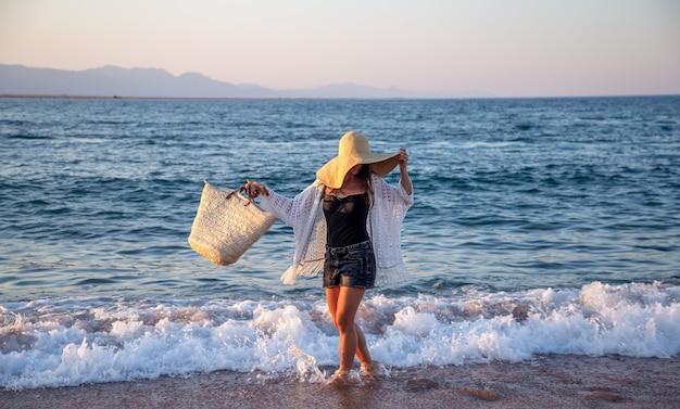 큰 모자와 고리 버들 가방을 든 소녀가 해안을 따라 걷습니다. 여름 휴가 개념.