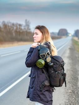 Девушка с черным противогазом на плече стоит на краю загородной трассы. девушка пытается остановить проезжающие машины, чтобы покинуть город, в котором эпидемия коронавируса.