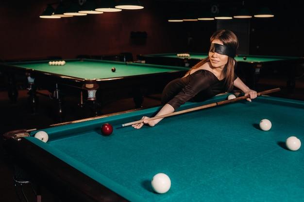 눈가리개와 당구 클럽에서 그녀의 손에 큐를 가진 소녀. 러시아 당구.