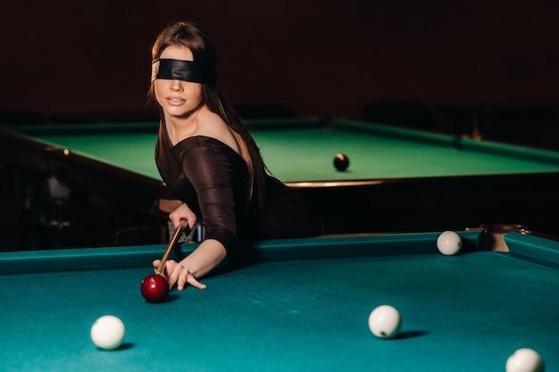ビリヤードクラブで目隠しとキューを手に持った女の子ロシアンビリヤード