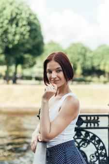Девушка с кавказской прической каре гуляет в городском парке по мосту и смотрит в камеру.