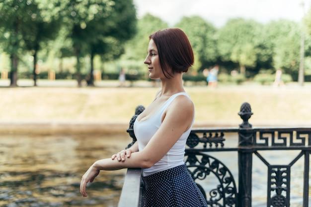 Девушка с кавказской прической каре гуляет в городском парке по мосту и смотрит в сторону.