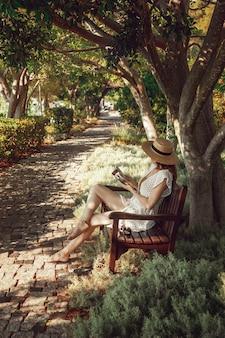 손에 책을 든 소녀가 그림 같은 나무 그늘 아래 벤치에 앉아있다. 생활 양식. 나무 그늘, 리조트 마을 gocek, 터키에서 휴식하는 젊은 여자