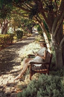 손에 책을 든 소녀가 그림 같은 나무 그늘 아래 벤치에 앉아있다. 생활 양식.