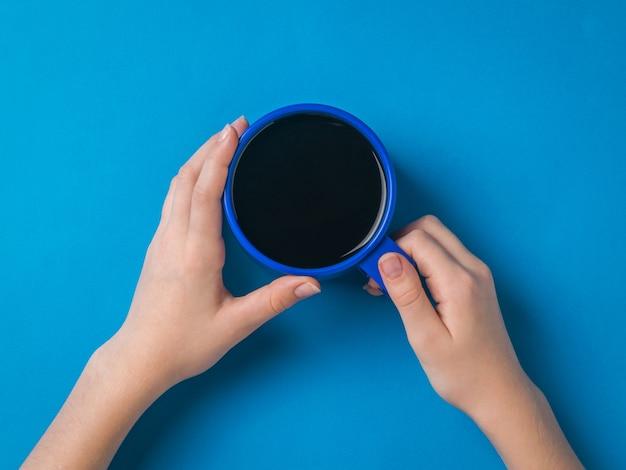파란색 표면에 그녀의 손에 밝은 파란색 커피 잔을 가진 소녀. 인기있는 상쾌한 음료를 들고있는 여성의 손.