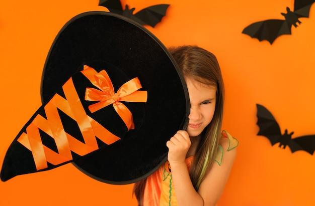 교활한 사악한 얼굴을 한 소녀가 할로윈에 마녀 오두막으로 한쪽 눈을 가립니다
