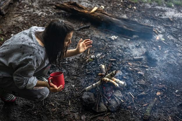 Девушка с чашкой в руке раздувает огонь, чтобы согреться.