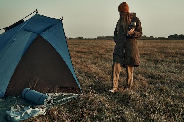 컵을 든 소녀가 천막 근처에 서 있습니다. 여행 및 캠핑.