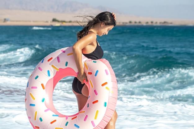海沿いにドーナツ型の水泳サークルを持つ少女。休暇中のレジャーとエンターテイメントの概念。