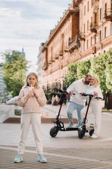 그녀의 손에 음료수를 든 소녀가 도시에 서 있고 전기 스쿠터를 탄 그녀의 뒤에는 부모님이 있습니다.