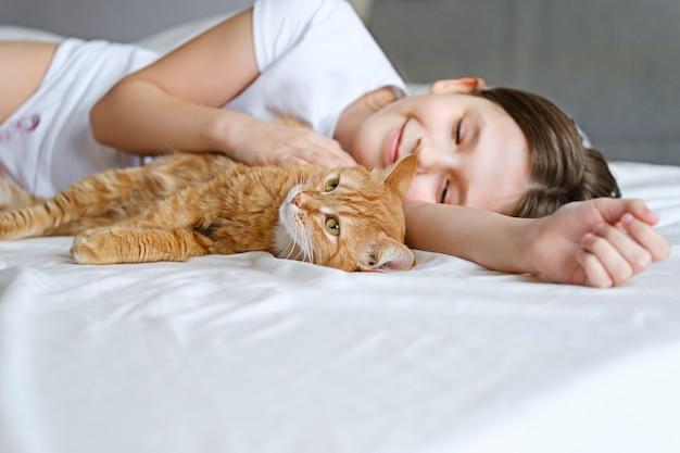 Девушка с рыжим котом лежит на белой кровати. молодая девушка гладит рыжего кота, лежа на белой простыне