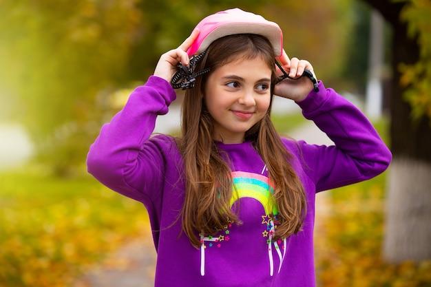 幸せな笑顔の女の子は、秋の公園でサイクリングするために丈夫なヘルメットをかぶっています。休息と時間の概念の護衛。
