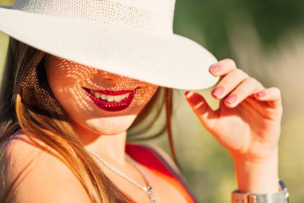 얼굴의 큰 절반을 덮는 모자를 쓴 소녀와 아름다운 화창한 날에 백설 공주 미소 만