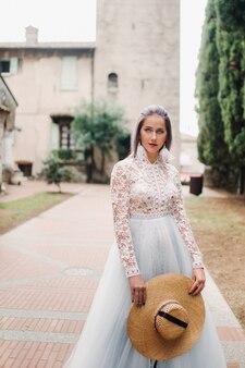 白いドレスを着た帽子をかぶった少女がシルミオーネの旧市街に立っています。イタリア。
