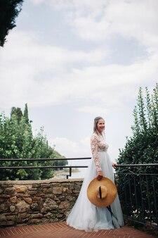 シルミオーネの旧市街に白いドレスを着た帽子をかぶった少女が立っている